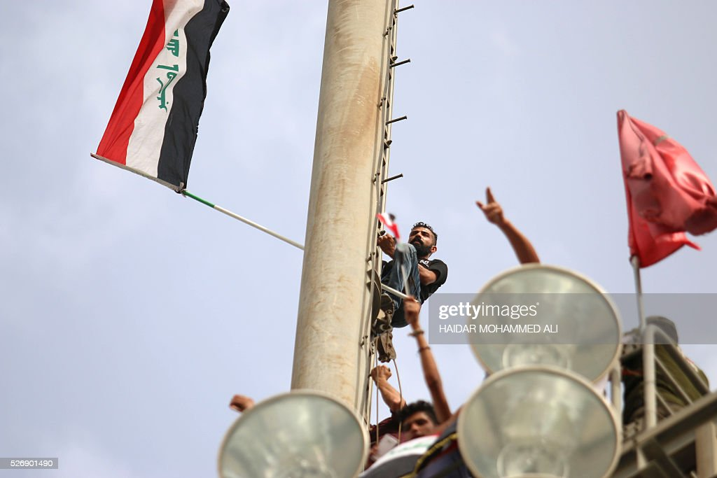 Iraqi protesters climb up a slope with their national flags in Baghdad's heavily fortified 'Green Zone' on May 1, 2016, a day after supporters of Shiite cleric Moqtada al-Sadr broke into the area after lawmakers again failed to approve new ministers. Protesters were withdrawing from Baghdad's Green Zone after breaking into the fortified area and storming Iraq's parliament in an unprecedented security breach the day before. The move, which lessens the pressure on politicians in Baghdad, came as rare bombings in the south killed 33 people and wounded dozens. / AFP / HAIDAR