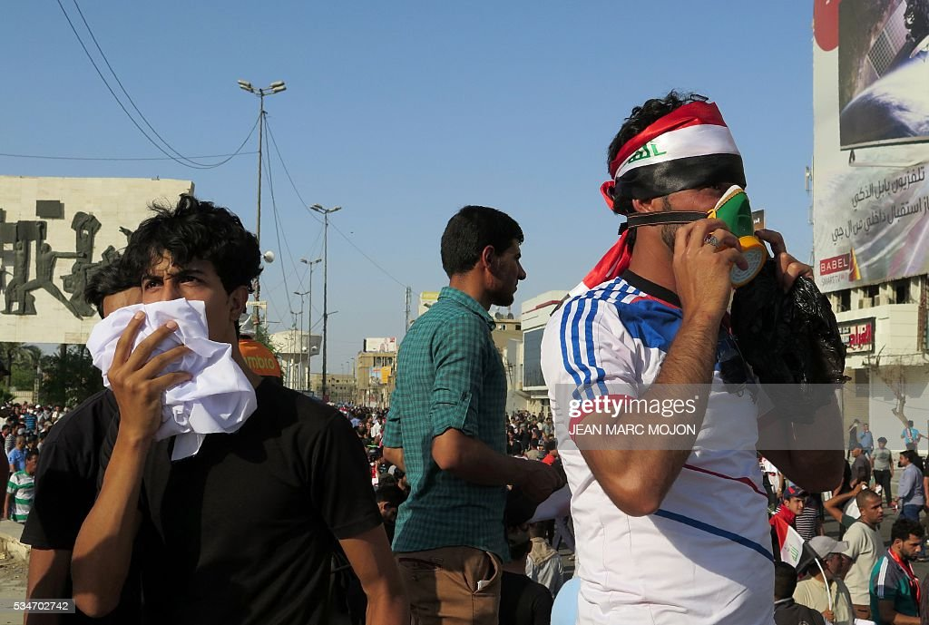 Iraqi protesters wearing surgical masks attend a demonstration at Tahrir square in Baghdad on May 27, 2016 defying a call by Iraqi prime minister to halt protests while security forces are battling the Islamic State group in Fallujah. Security forces fired tear gas as thousands of protesters gathered in central Baghdad and attempted to head to the Green Zone, a fortified area they have breached twice in the last month. / AFP / Jean Marc MOJON