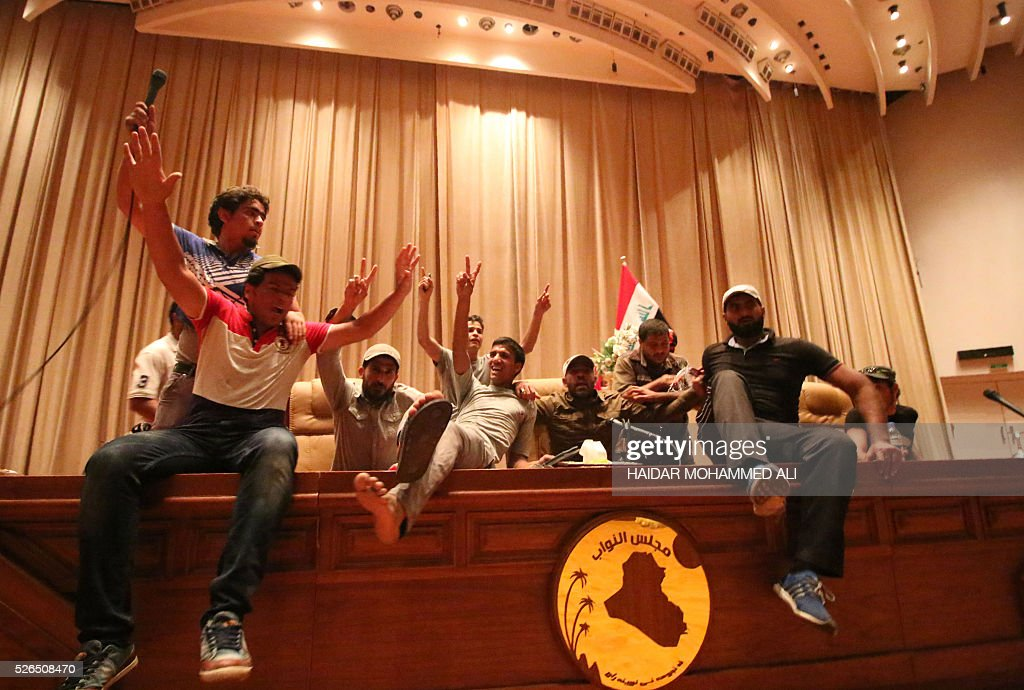 Iraqi protesters flash the V-sign as they gather inside the parliament after breaking into Baghdad's heavily fortified 'Green Zone' on April 30, 2016. A protest held outside the Green Zone escalated after parliament again failed to reach a quorum and approve new ministers to replace the current government of party-affiliated ministers. / AFP / HAIDAR