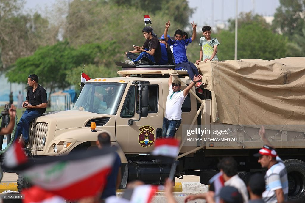 Iraqi protesters gather around a special forces vehicle outside the parliament in Baghdad's heavily fortified 'Green Zone' on May 1, 2016, a day after supporters of Shiite cleric Moqtada al-Sadr broke into the area after lawmakers again failed to approve new ministers. Protesters were withdrawing from Baghdad's Green Zone after breaking into the fortified area and storming Iraq's parliament in an unprecedented security breach the day before. The move, which lessens the pressure on politicians in Baghdad, came as rare bombings in the south killed 33 people and wounded dozens. / AFP / HAIDAR