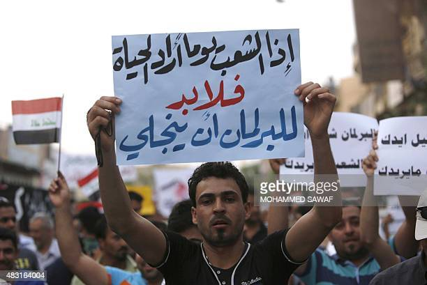 Iraqi protesters hold placards and shout slogans during a demonstration against corruption and poor services on August 6 in the Shiite shrine city of...