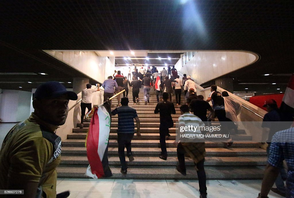 Iraqi protesters holding national flags gather inside the parliament after braking into Baghdad's heavily fortified 'Green Zone' on April 30, 2016. A protest held outside the Green Zone escalated after parliament again failed to reach a quorum and approve new ministers to replace the current government of party-affiliated ministers. / AFP / HAIDAR