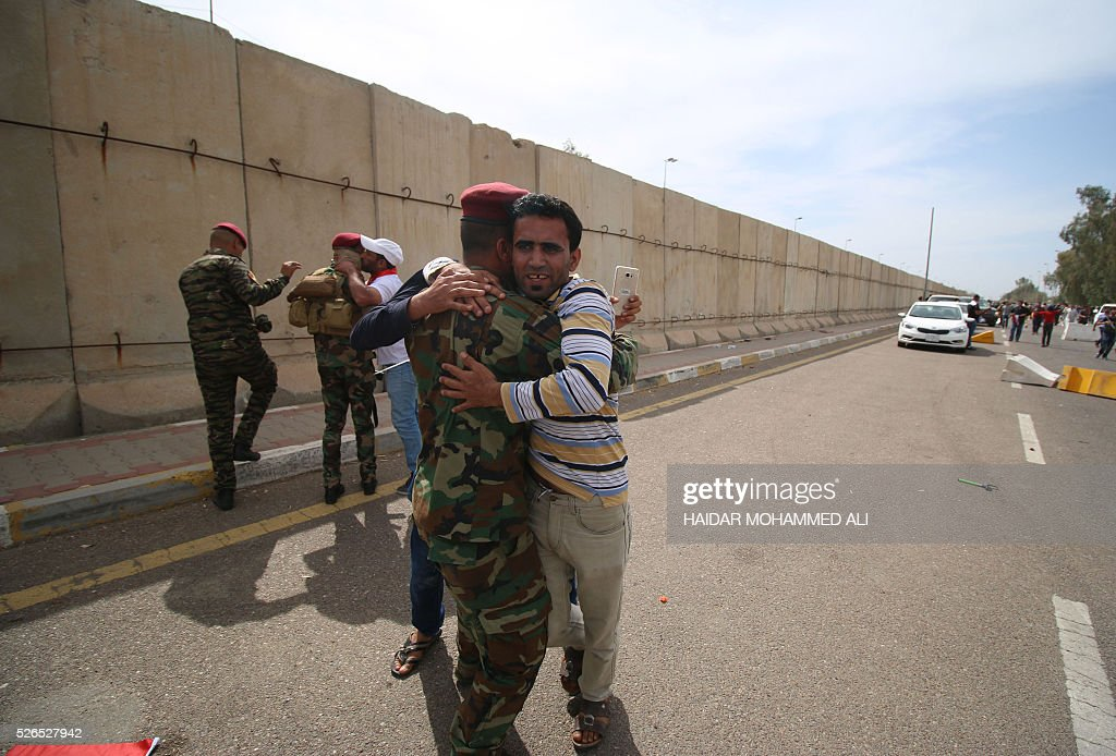 Iraqi protesters hug members of the security forces as they head to the parliament after breaking into Baghdad's heavily fortified 'Green Zone' on April 30, 2016. Thousands of angry protesters broke into Baghdad's Green Zone and stormed the parliament building after lawmakers again failed to approve new ministers. Jubilant supporters of cleric Moqtada al-Sadr invaded the main session hall, shouting slogans glorifying their leader and claiming that they had rooted out corruption. / AFP / HAIDAR