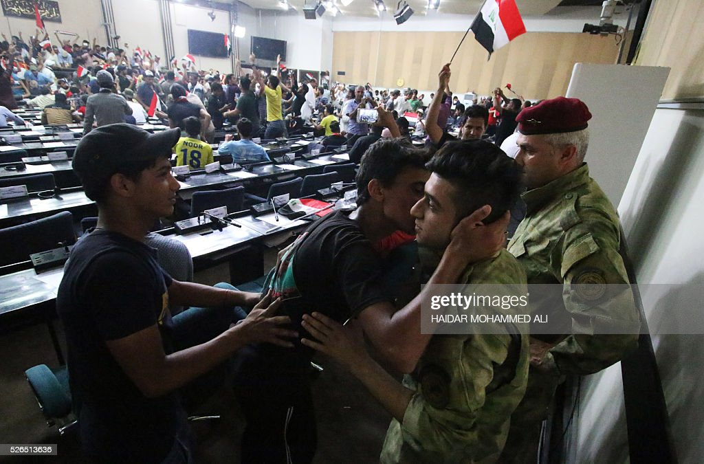 Iraqi protesters kiss members of the security forces as they gather inside the parliament after breaking into Baghdad's heavily fortified 'Green Zone' on April 30, 2016. Thousands of angry protesters broke into Baghdad's Green Zone and stormed the parliament building after lawmakers again failed to approve new ministers. Jubilant supporters of cleric Moqtada al-Sadr invaded the main session hall, shouting slogans glorifying their leader and claiming that they had rooted out corruption. / AFP / HAIDAR