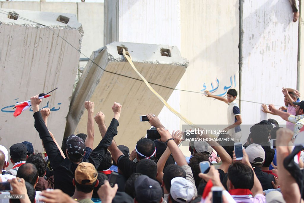 Iraqi protesters open a breach in a concrete wall surrounding the parliament after breaking into Baghdad's heavily fortified 'Green Zone' on April 30, 2016. Thousands of angry protesters broke into Baghdad's Green Zone and stormed the parliament building after lawmakers again failed to approve new ministers. Jubilant supporters of cleric Moqtada al-Sadr invaded the main session hall, shouting slogans glorifying their leader and claiming that they had rooted out corruption. / AFP / HAIDAR
