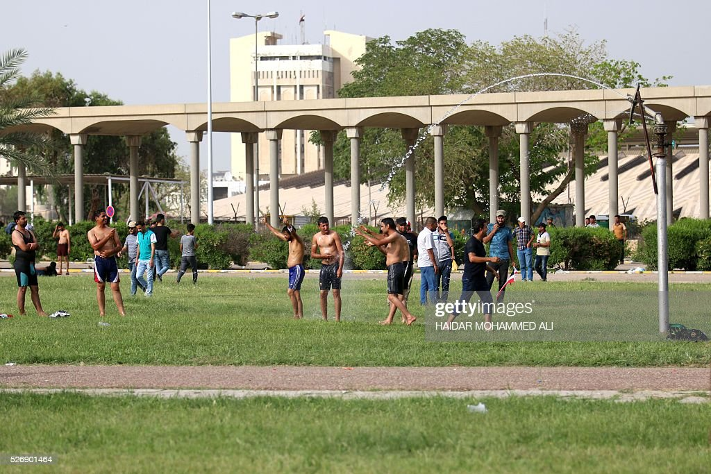 Iraqi protesters play in the yard close to the 'Crossed Swords monument' in Baghdad's heavily fortified 'Green Zone' on May 1, 2016, a day after supporters of Shiite cleric Moqtada al-Sadr broke into the area after lawmakers again failed to approve new ministers. Protesters were withdrawing from Baghdad's Green Zone after breaking into the fortified area and storming Iraq's parliament in an unprecedented security breach the day before. The move, which lessens the pressure on politicians in Baghdad, came as rare bombings in the south killed 33 people and wounded dozens. / AFP / HAIDAR