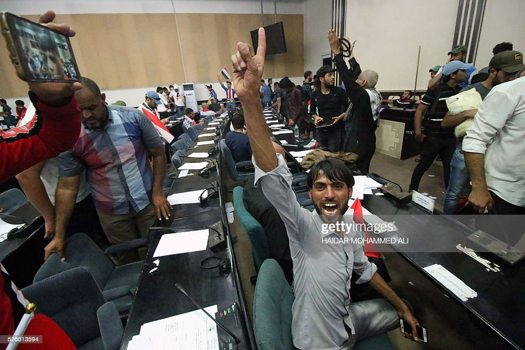 Iraqi protesters shout slogans as they sit inside the parliament after breaking into Baghdad's heavily fortified 'Green Zone' on April 30, 2016. Thousands of angry protesters broke into Baghdad's Green Zone and stormed the parliament building after lawmakers again failed to approve new ministers. Jubilant supporters of cleric Moqtada al-Sadr invaded the main session hall, shouting slogans glorifying their leader and claiming that they had rooted out corruption. / AFP / HAIDAR