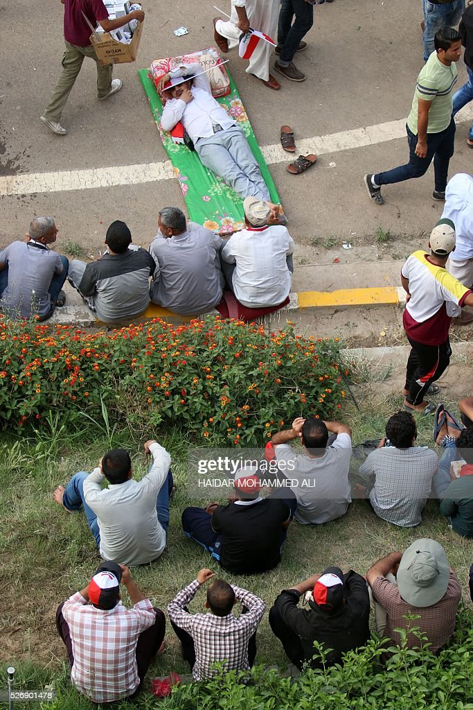 Iraqi protesters sit in in Baghdad's heavily fortified 'Green Zone' on May 1, 2016, a day after supporters of Shiite cleric Moqtada al-Sadr broke into the area after lawmakers again failed to approve new ministers. Protesters were withdrawing from Baghdad's Green Zone after breaking into the fortified area and storming Iraq's parliament in an unprecedented security breach the day before. The move, which lessens the pressure on politicians in Baghdad, came as rare bombings in the south killed 33 people and wounded dozens. / AFP / HAIDAR