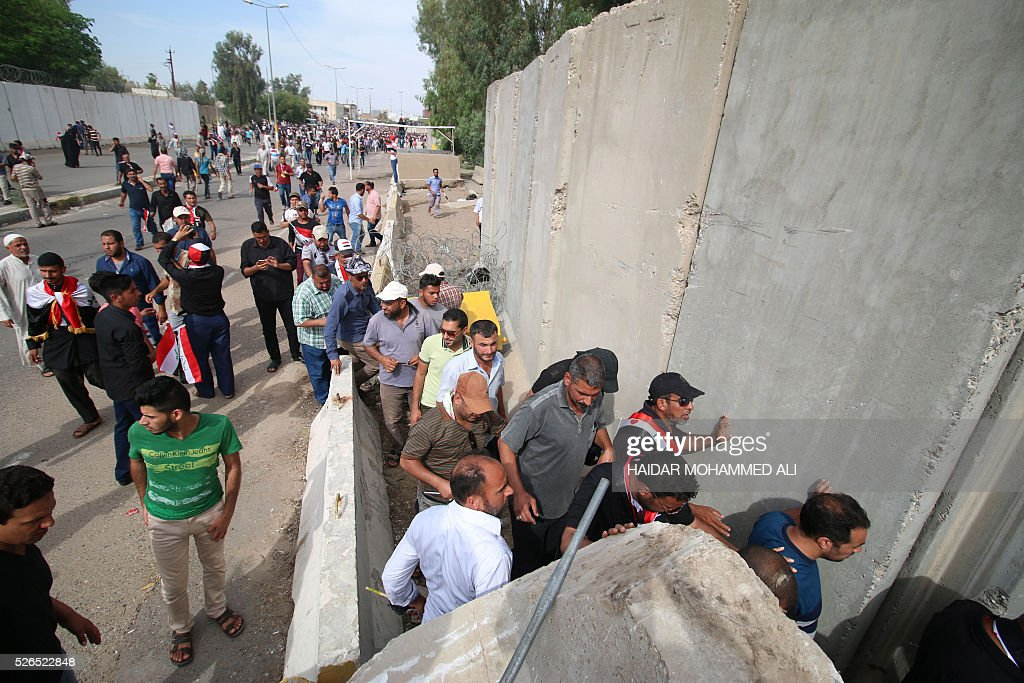 Iraqi protesters stand next to a concrete wall as they look for an access to the parliament after breaking into Baghdad's heavily fortified 'Green Zone' on April 30, 2016. Thousands of angry protesters broke into Baghdad's Green Zone and stormed the parliament building after lawmakers again failed to approve new ministers. Jubilant supporters of cleric Moqtada al-Sadr invaded the main session hall, shouting slogans glorifying their leader and claiming that they had rooted out corruption. / AFP / HAIDAR