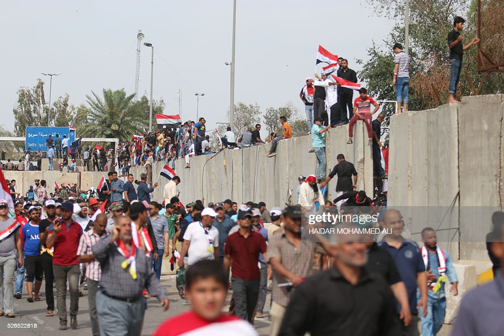 Iraqi protesters stand on a concrete wall surrounding the parliament after breaking into Baghdad's heavily fortified 'Green Zone' on April 30, 2016. Thousands of angry protesters broke into Baghdad's Green Zone and stormed the parliament building after lawmakers again failed to approve new ministers. Jubilant supporters of cleric Moqtada al-Sadr invaded the main session hall, shouting slogans glorifying their leader and claiming that they had rooted out corruption. / AFP / HAIDAR