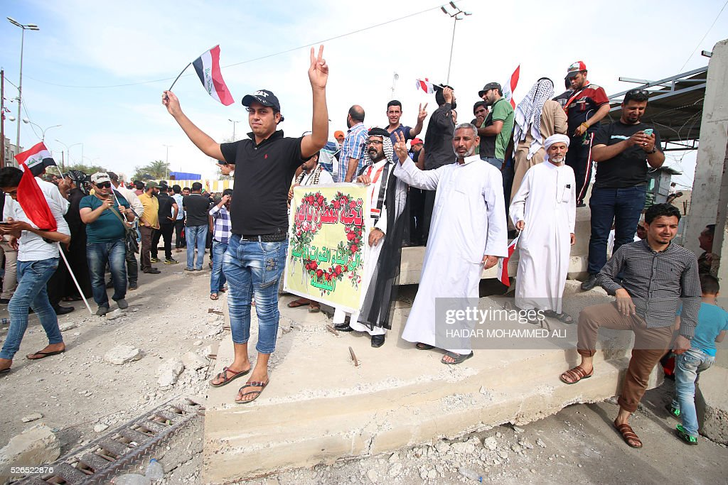 Iraqi protesters stand on a part of a collapsed concrete wall after breaking into Baghdad's heavily fortified 'Green Zone' on April 30, 2016. Thousands of angry protesters broke into Baghdad's Green Zone and stormed the parliament building after lawmakers again failed to approve new ministers. Jubilant supporters of cleric Moqtada al-Sadr invaded the main session hall, shouting slogans glorifying their leader and claiming that they had rooted out corruption. / AFP / HAIDAR