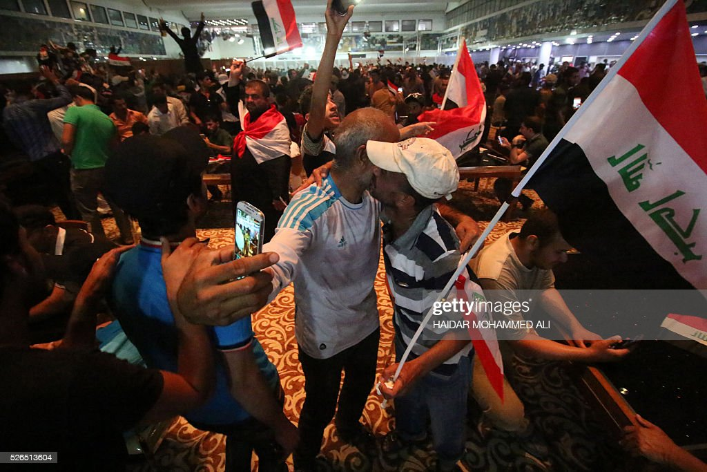 Iraqi protesters take a selfie as they gather inside the parliament after breaking into Baghdad's heavily fortified 'Green Zone' on April 30, 2016. Thousands of angry protesters broke into Baghdad's Green Zone and stormed the parliament building after lawmakers again failed to approve new ministers. Jubilant supporters of cleric Moqtada al-Sadr invaded the main session hall, shouting slogans glorifying their leader and claiming that they had rooted out corruption. / AFP / HAIDAR