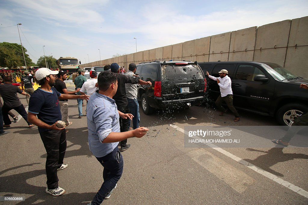 Iraqi protesters throw stones at a vehicle they believe belongs to a lawmaker after they broke into Baghdad's heavily fortified 'Green Zone' and headed to the parliament on April 30, 2016. A protest held outside the Green Zone escalated after parliament again failed to reach a quorum and approve new ministers to replace the current government of party-affiliated ministers. / AFP / HAIDAR