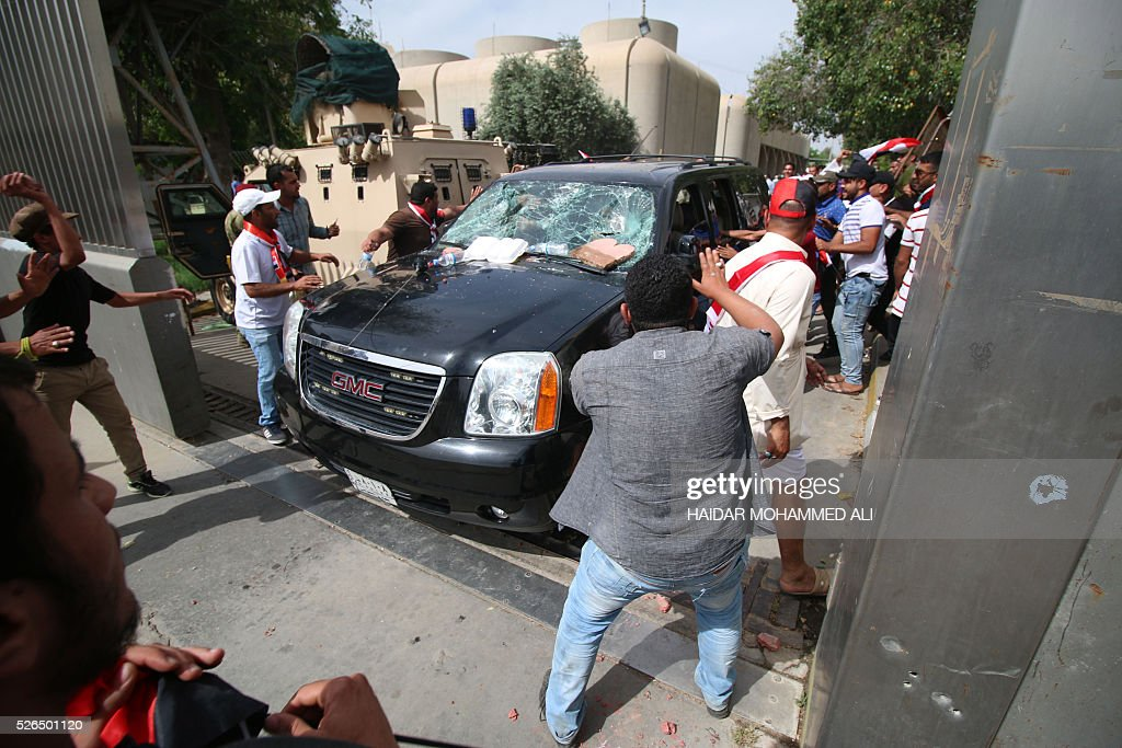 Iraqi protesters throw stones at a vehicle they believe belongs to a lawmaker as they gather outside the parliament after braking into Baghdad's heavily fortified 'Green Zone' on April 30, 2016. A protest held outside the Green Zone escalated after parliament again failed to reach a quorum and approve new ministers to replace the current government of party-affiliated ministers. / AFP / HAIDAR
