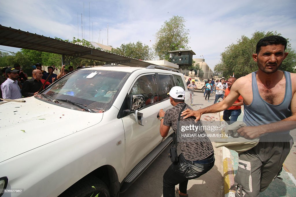 Iraqi protesters throw stones at a vehicle they believe belongs to a lawmaker as they gather outside the parliament after breaking into Baghdad's heavily fortified 'Green Zone' on April 30, 2016. Thousands of angry protesters broke into Baghdad's Green Zone and stormed the parliament building after lawmakers again failed to approve new ministers. Jubilant supporters of cleric Moqtada al-Sadr invaded the main session hall, shouting slogans glorifying their leader and claiming that they had rooted out corruption. / AFP / HAIDAR