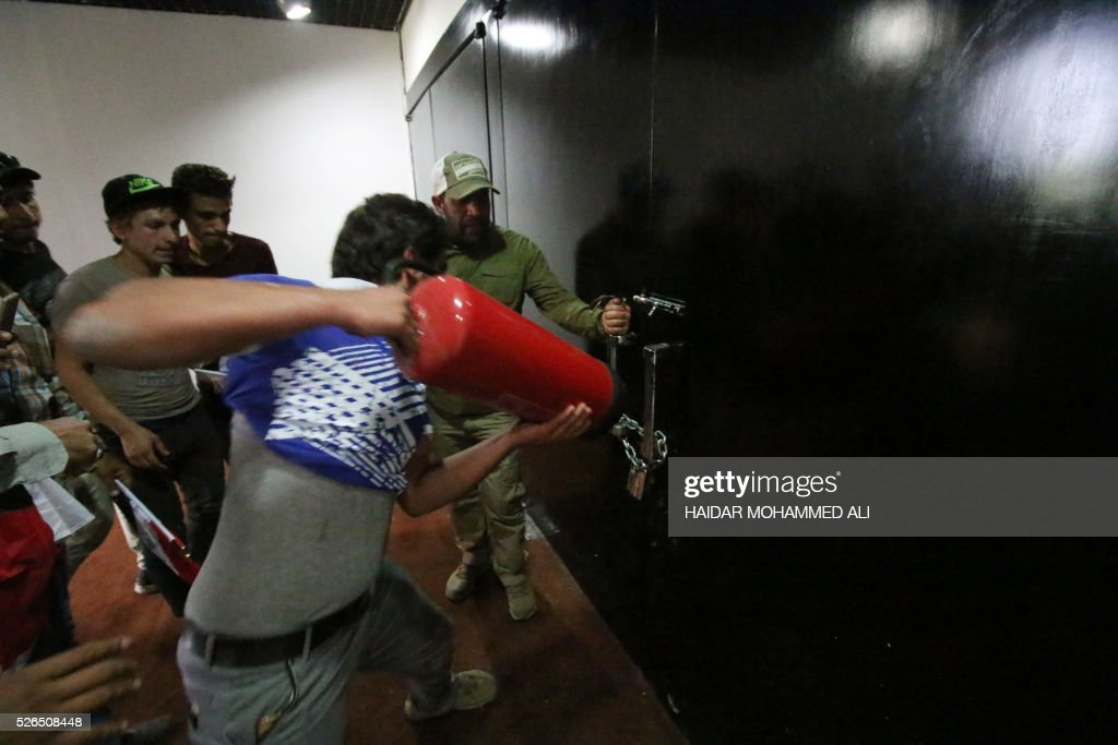 Iraqi protesters use a fire extinguisher to open a door inside the parliament after breaking into Baghdad's heavily fortified 'Green Zone' on April 30, 2016. A protest held outside the Green Zone escalated after parliament again failed to reach a quorum and approve new ministers to replace the current government of party-affiliated ministers. / AFP / HAIDAR