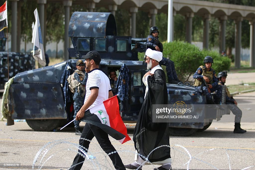 Iraqi protesters walk past security forces outside the parliament in Baghdad's heavily fortified 'Green Zone' on May 1, 2016, a day after supporters of Shiite cleric Moqtada al-Sadr broke into the area after lawmakers again failed to approve new ministers. Protesters were withdrawing from Baghdad's Green Zone after breaking into the fortified area and storming Iraq's parliament in an unprecedented security breach the day before. The move, which lessens the pressure on politicians in Baghdad, came as rare bombings in the south killed 33 people and wounded dozens. / AFP / HAIDAR