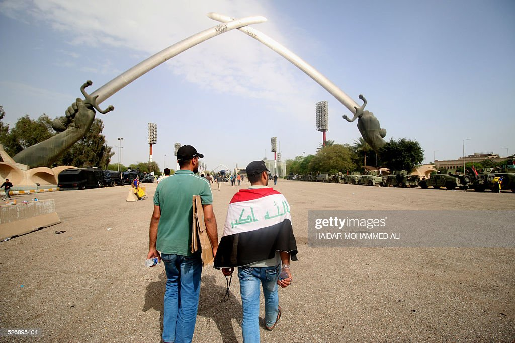 Iraqi protesters walk towards the 'Crossed Swords monument' in Baghdad's heavily fortified 'Green Zone' on May 1, 2016, a day after supporters of Shiite cleric Moqtada al-Sadr broke into the area after lawmakers again failed to approve new ministers. Protesters were withdrawing from Baghdad's Green Zone after breaking into the fortified area and storming Iraq's parliament in an unprecedented security breach the day before. The move, which lessens the pressure on politicians in Baghdad, came as rare bombings in the south killed 33 people and wounded dozens. / AFP / HAIDAR