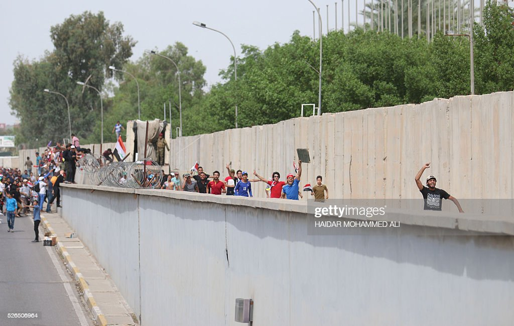 Iraqi protesters wave national flags and shout slogans after braking into Baghdad's heavily fortified 'Green Zone' on April 30, 2016. A protest held outside the Green Zone escalated after parliament again failed to reach a quorum and approve new ministers to replace the current government of party-affiliated ministers. / AFP / HAIDAR