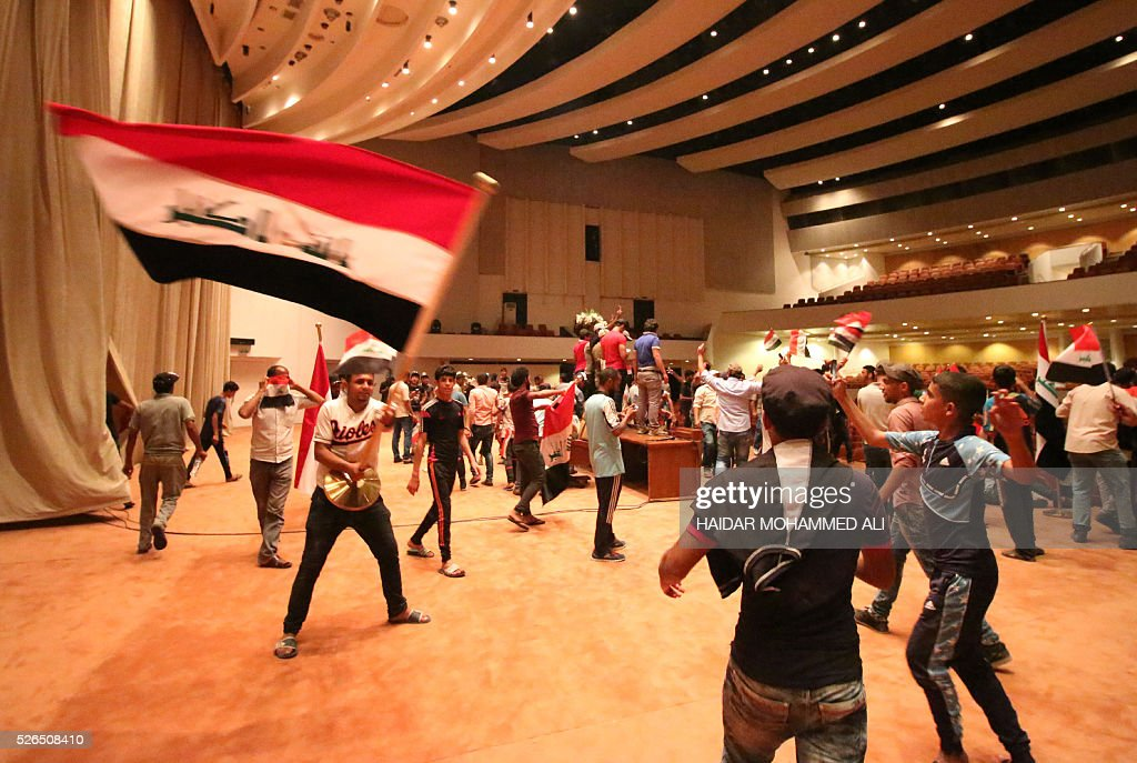 Iraqi protesters wave national flags as they gather inside the parliament after breaking into Baghdad's heavily fortified 'Green Zone' on April 30, 2016. A protest held outside the Green Zone escalated after parliament again failed to reach a quorum and approve new ministers to replace the current government of party-affiliated ministers. / AFP / HAIDAR
