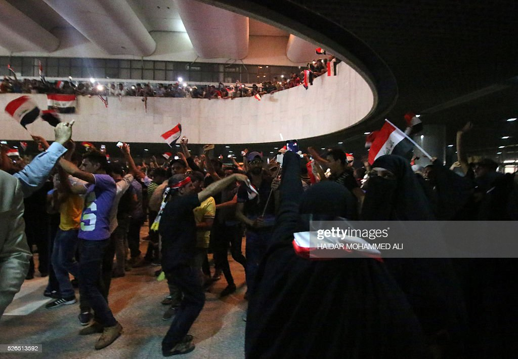 Iraqi protesters wave national flags as they gather inside the parliament after breaking into Baghdad's heavily fortified 'Green Zone' on April 30, 2016. Thousands of angry protesters broke into Baghdad's Green Zone and stormed the parliament building after lawmakers again failed to approve new ministers. Jubilant supporters of cleric Moqtada al-Sadr invaded the main session hall, shouting slogans glorifying their leader and claiming that they had rooted out corruption. / AFP / HAIDAR