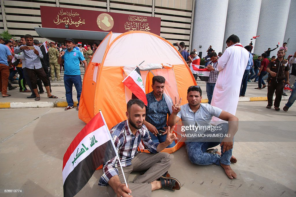 Iraqi protesters wave national flags as they gather outside the parliament after breaking into Baghdad's heavily fortified 'Green Zone' on April 30, 2016. Thousands of angry protesters broke into Baghdad's Green Zone and stormed the parliament building after lawmakers again failed to approve new ministers. Jubilant supporters of cleric Moqtada al-Sadr invaded the main session hall, shouting slogans glorifying their leader and claiming that they had rooted out corruption. / AFP / HAIDAR