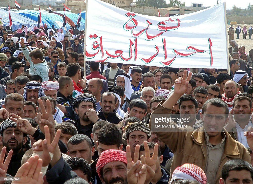 Iraqi protestors hold a sign reading in Arabic: 'Revolution of free Iraqis' as others flash the sign for victory during a demonstration against Iraq's subordination to Iran in the northern Iraqi town of Hawijah, south of the ethnically mixed city of Kirkuk, on March 8, 2013. Iraqi security forces fired on anti-government protesters in the main northern city of Mosul, killing at least one and wounding others, activists said.