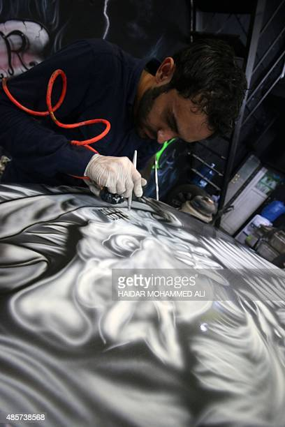 Iraqi Raeed Jamal uses a spray gun to custom paint a car on August 29 2015 at his workshop in the upmarket Mansur district of Baghdad AFP PHOTO /...