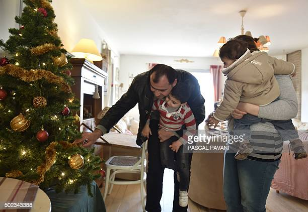 Iraqi Rami and his family stand next to a Christmas Tree in their living room in Pibrac in the HauteGaronne region on December 23 2015 The Iraqi...