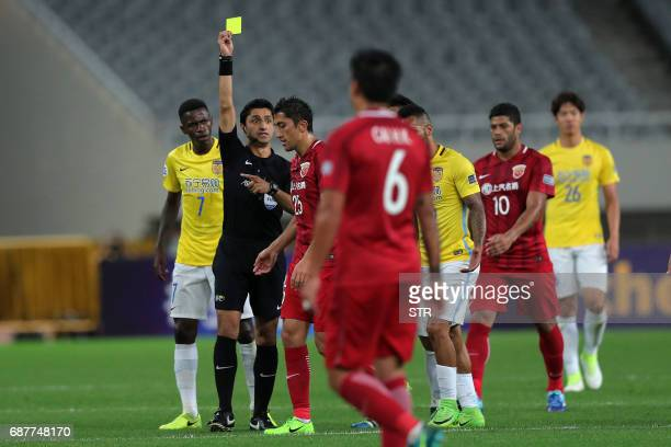 Iraqi referee Mohanad Qassim gives a yellow card to Akhmedov Odil of China's Shanghai SIPG during the AFC Champions League round of 16 football match...