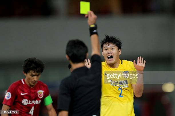 Iraqi referee Mohanad Qassim gives a yellow card to Li Ang of China's Jiangsu FC during the AFC Champions League round of 16 football match against...