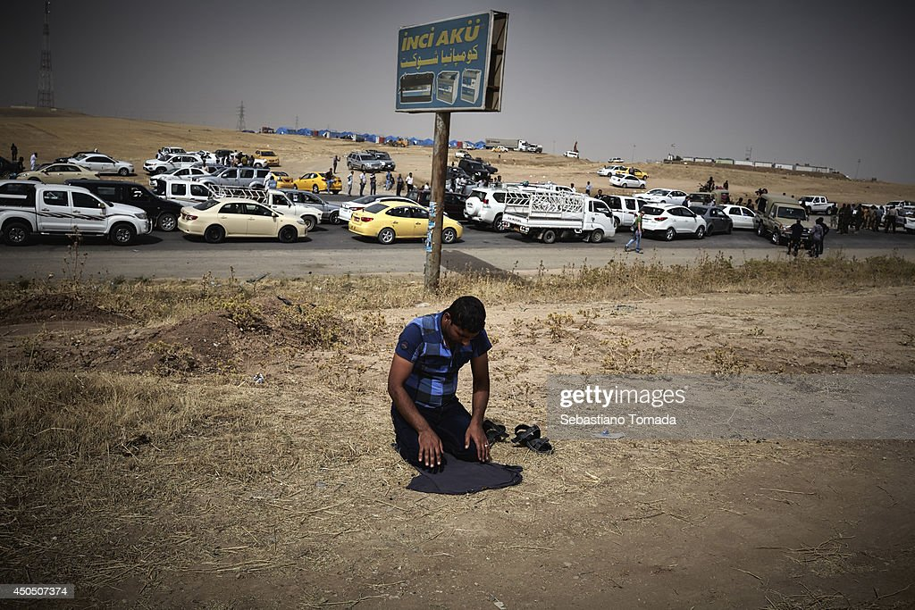 A Iraqi refugee fleeing from the city of Mosul prays at a checkpoint as he awaits for hours before entering Kurdistan. June 12, 2014.