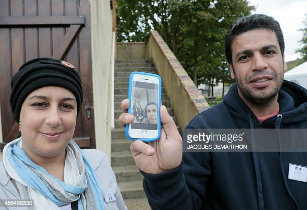 Iraqi refugees Ali Merkath and his wife Tahrir show a selfie picture taken on September 12 2015 when French president Hollande came for visiting...