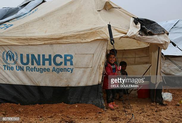 Iraqi refugees mostly fleeing the northern city of Mosul now held by the Islamic State group stand at a new camp on the outskirts of the Syrian town...