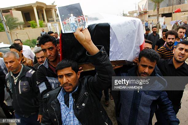 Iraqi relatives and friends carry the coffin of one of the victims of a suicide bomb attack in a nearby village the day before during funeral on...
