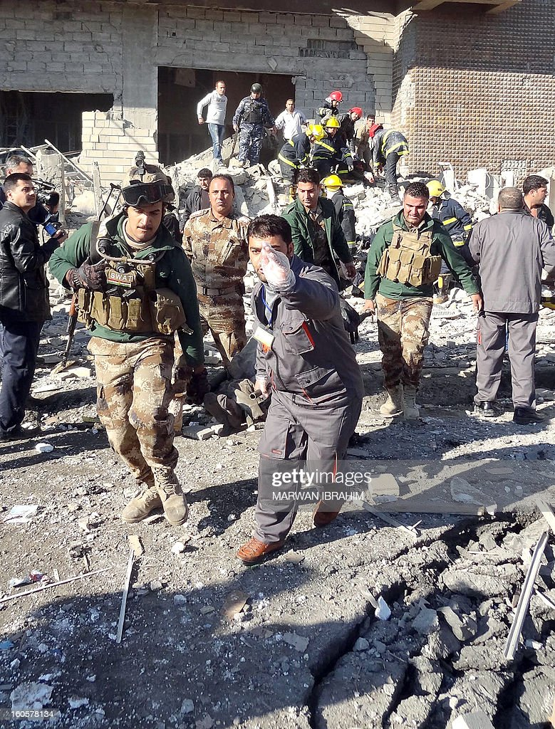 Iraqi rescuers carry a stretcher from the scene after a car bombing followed by an assault by grenade-throwing gunmen on a police headquarters in a disputed northern city of Kirkuk, on February 3, 2013, killing some 30 people. The vehicle that was detonated in the center of the city was painted to appear as though it was a police car, and the militants who sought to seize the compound were dressed as policemen, witnesses said.