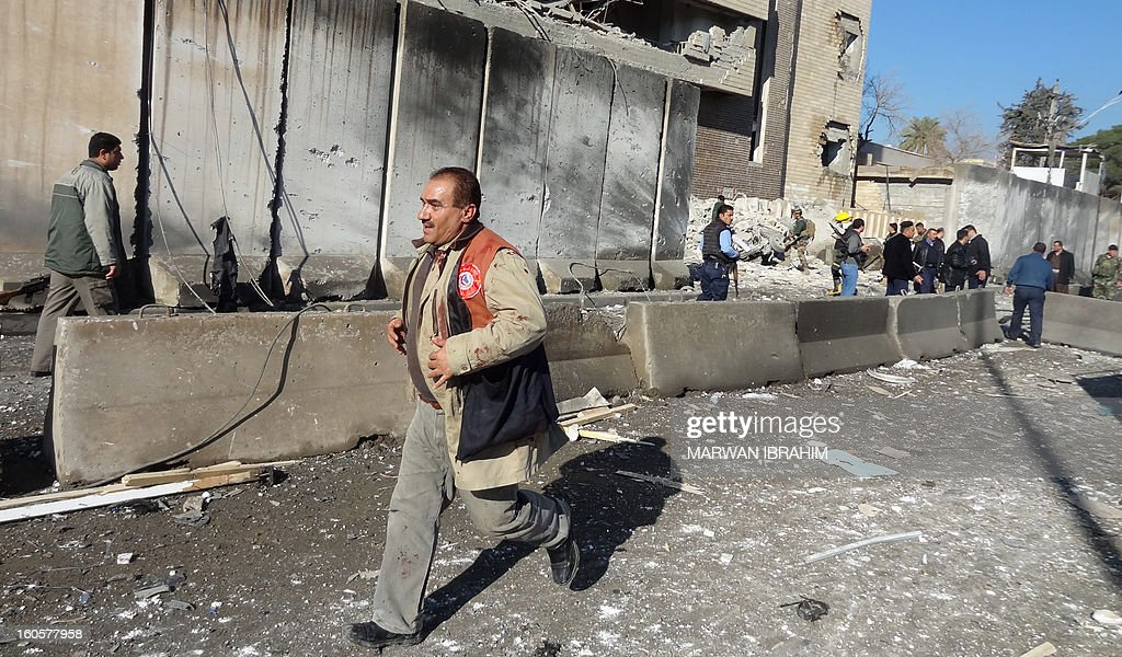 Iraqi rescuers runs at the scene after a car bombing followed by an assault by grenade-throwing gunmen on a police headquarters in a disputed northern city of Kirkuk, on February 3, 2013, killing some 30 people. The vehicle that was detonated in the center of the city was painted to appear as though it was a police car, and the militants who sought to seize the compound were dressed as policemen, witnesses said. AFP PHOTO/MARWAN IBRAHIM