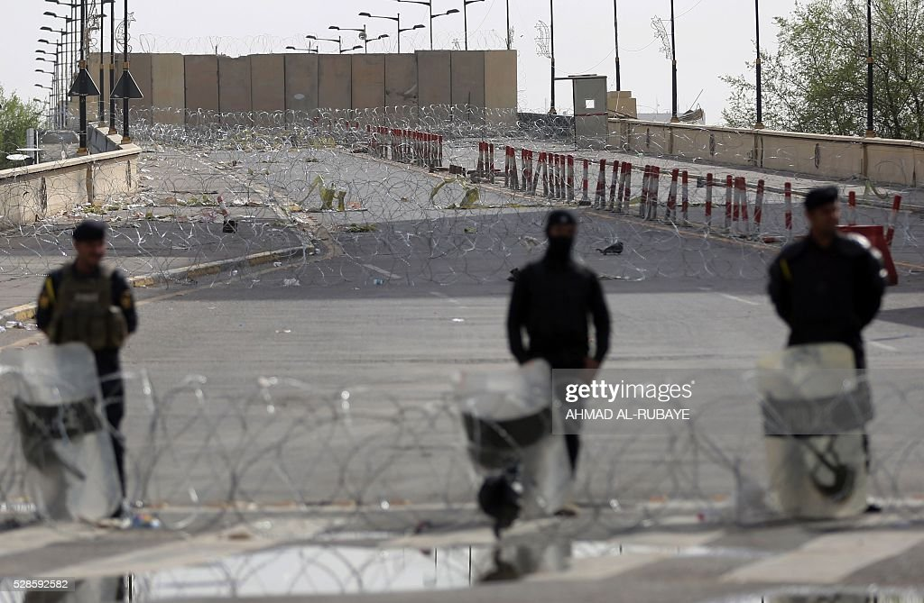 Iraqi riot police stand guard at the Jumhuriyah Bridge, a route leading from Tahrir Square to the Green Zone, on May 6, 2016, a week after Moqtada al-Sadr protesters broke into the fortified Green Zone and stormed the parliament. A major demonstration failed to materialise in central Baghdad as Iraq deployed riot police and armoured vehicles to keep protesters away from the Green Zone, which they breached last week. Only a few dozen demonstrators turned out in Baghdad's Tahrir Square, and they did not challenge the riot police blocking them from heading toward the fortified Green Zone area. Protesters had threatened to return to the restricted area in the heart of Baghdad, as they did on April 30 when they stormed parliament in anger at lawmakers' failure to approve new ministers. / AFP / AHMAD