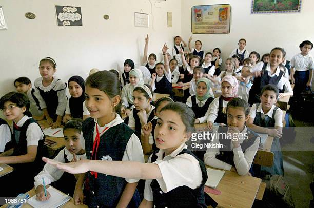 Iraqi school girls raise their hands to answer a teacher's questions in their classroom May 10 2003 in Baghdad Iraq One month after the collapse of...