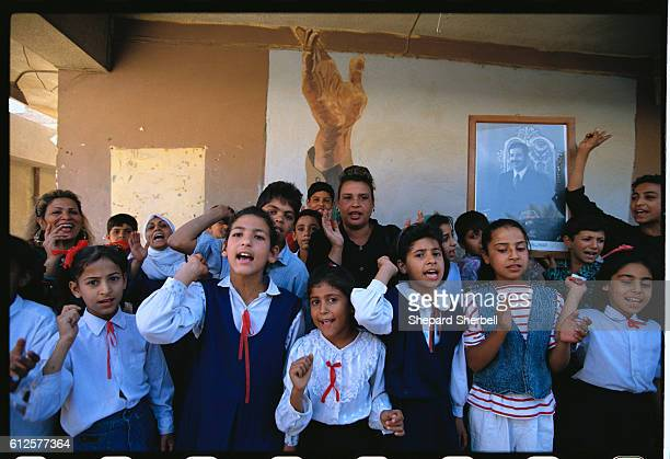 Iraqi schoolchildren rally for Saddam Hussein during the voting in the presidential referendum