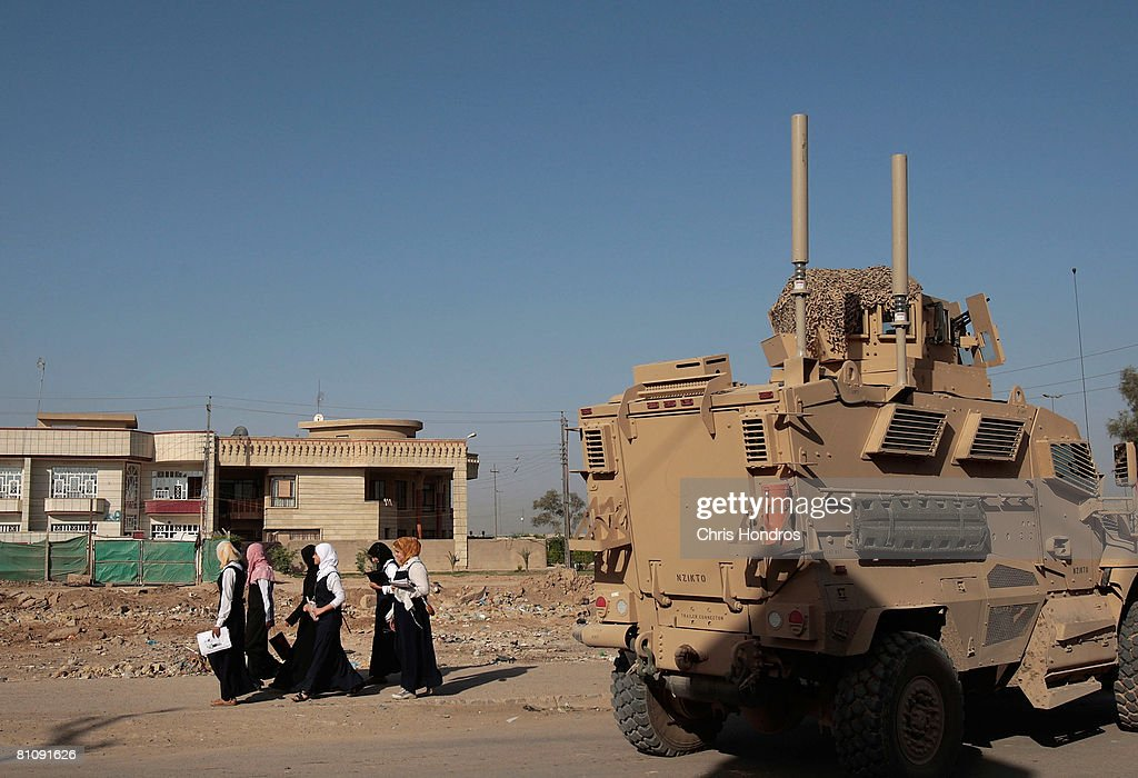 Iraqi schoolgirls walk past a US Army MRAP vehicle during a morning patrol in the Baladiyat neighborhood May 15, 2008 in Baghdad, Iraq. 10th Mountain Division soldier in the area take daily joint patrols with the Iraqi National Police, in the ongoing effort to build up stable national Iraqi security institutions aligned with the national government.
