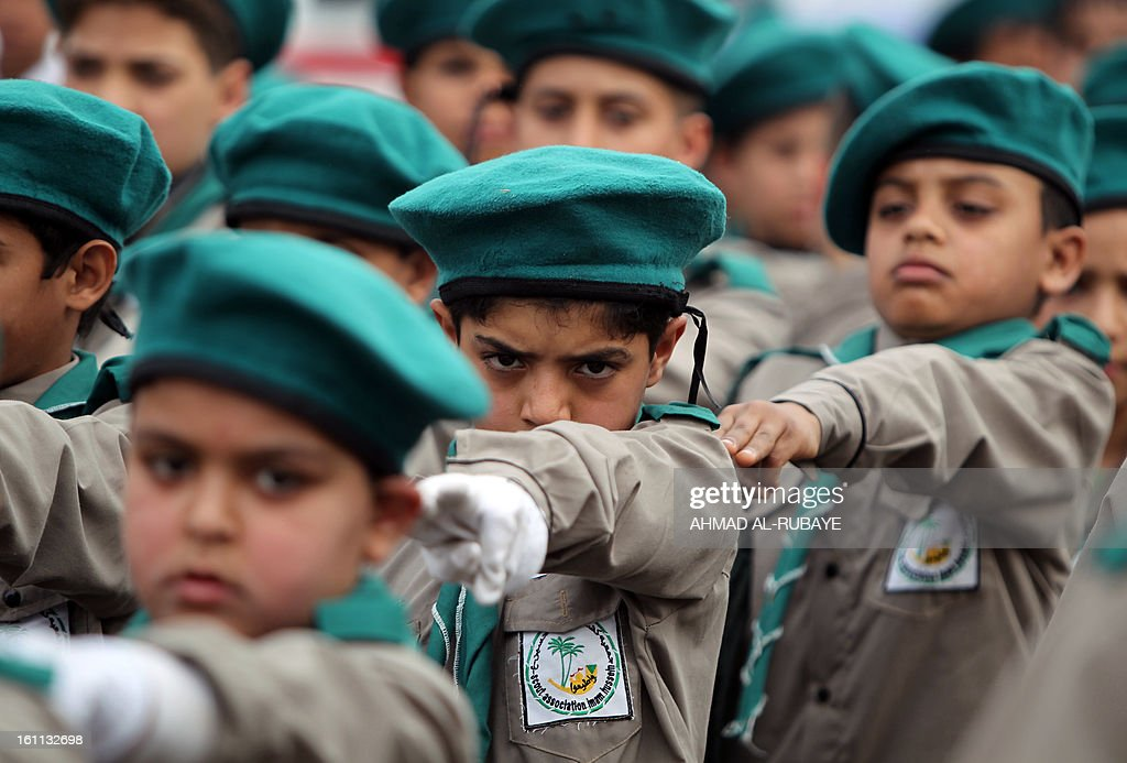 Iraqi scouts whose organization follows the Lebanese Hezbollah Shiite Muslim political party, march during a celebration in Baghdad on February 9, 2013, to commemorate the withdrawal of US troops' from Iraq in December 2011, ending nearly nine years of the mainly US led occupation of Iraq.