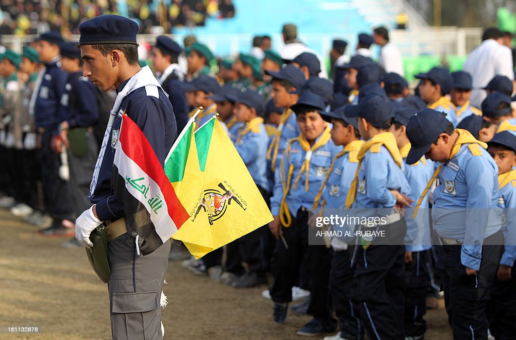 Iraqi scouts, whose organization follows the Lebanese Hezbollah Shiite Muslim political party, stand guard during a celebration in Baghdad on February 9, 2013, to commemorate the withdrawal of US troops' from Iraq in December 2011, ending nearly nine years of the mainly US led occupation of Iraq.