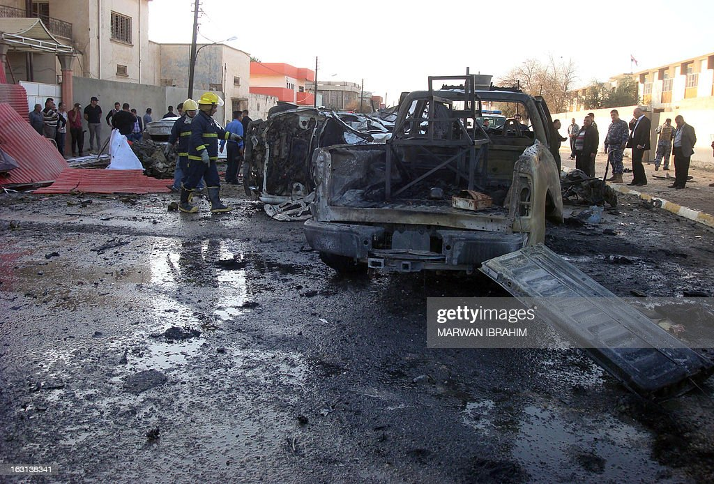 Iraqi security and fire fighters gather close to the debris following a car bomb, in the northern city of Kirkuk on March 5, 2013. Two car bombs targeted police in the northern city of Kirkuk, killing five and wounding at least 18, while gunmen killed a town council member and a North Oil Company employee south of the city, police and a health official said.