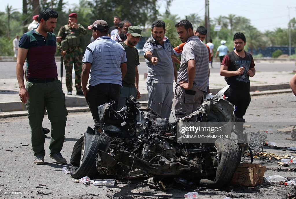 Iraqi security forces and civilians look at the damage following a car bomb targeting Shiite pilgrims heading to commemorate the death of Imam al-Kadhim in Baghdad's southern Saidiya neighbourhood on May 2, 2106. Many of the main thoroughfares in the ca[ital are closed in the days leading up to the annual commemoration of Imam Musa Kadhim's death, an important date in the Shiite Muslim calendar. ALI