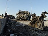 Iraqi security forces and gunmen inspect the wreckage of cars following a suicide bomb attack that killed at least seven people on September 17 in...