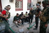 Iraqi security forces and gunmen rest on a sidewalk following clashes with jihadists on September 19 in Ramadi the capital of the western province of...