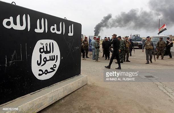 Iraqi security forces and Shiite fighters from the Popular Mobilisation units gather next to a mural depicting the emblem of the Islamic State group...