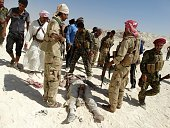 Iraqi security forces and Sunni tribesmen stand next to the body of an alleged Islamic State fighter after an attack at a military post during the...