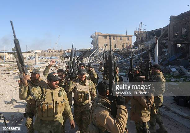 Iraqi security forces brandish their weapons on December 28 2015 at the heavily damaged Anbar police headquarters after they recaptured the city of...